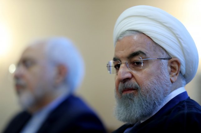 Iranian President Hassan Rouhani (R) appears at a ceremony Sunday in Tehran. In a televised speech, he warned President Donald Trump that threatening to block oil exports will lead to the mother of all wars. Photo courtesy of Iran presidential office/EPA