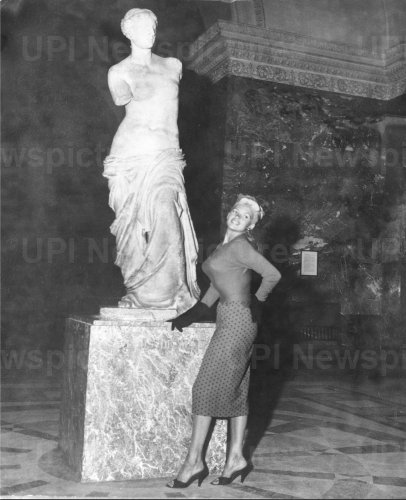 Jayne Mansfield poses below Venus of Milo at the Louvre