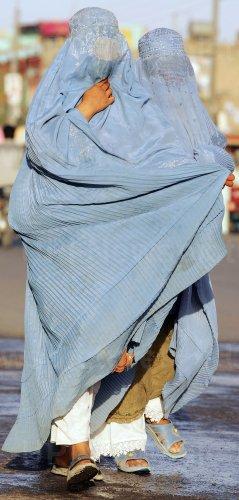 Two burqa-clad Afghan women walk through Walayat street in Herat, Afghanistan