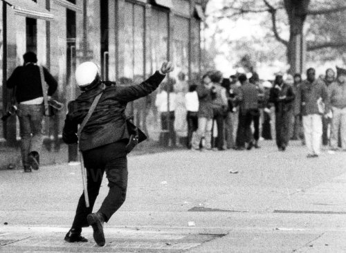 A policeman uses tear gas to contain a crowd of several hundred anti-Ku Klux Klan demonstrators.