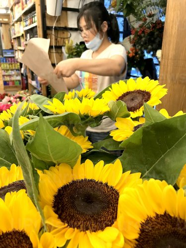 A florist at a flower shop prepares orders in Beijing, China