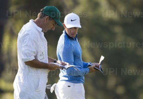 Rory McIlroy talks to his caddie at the Masters