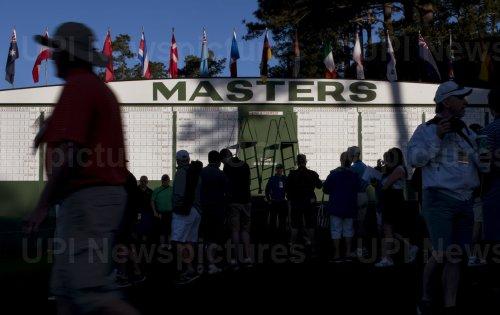 Patrons gather near the Masters Scoreboard at Augusta Naitonal
