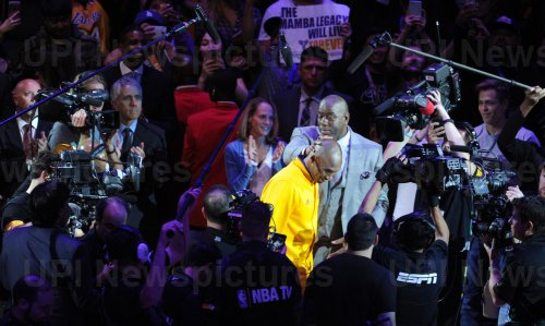 Los Angeles Lakers Kobe Bryant gets a pat on the head by Magic Johnson as he is introduced before his last game