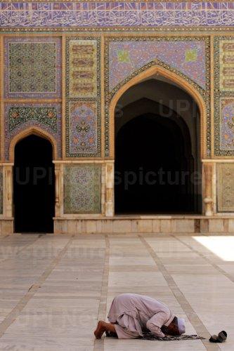 An Afghan man preys in Herat, Afghanistan