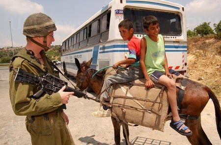 An Israeli soldier talks to Palestinian boys on a donkey at the Al Khader checkpoint near Bethlehem