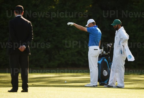 Michael Greller watches Jordan Spieth take a drop at the Masters