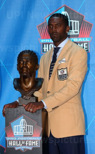 Ray Lewis poses with his bust at the Pro Football Hall of Fame