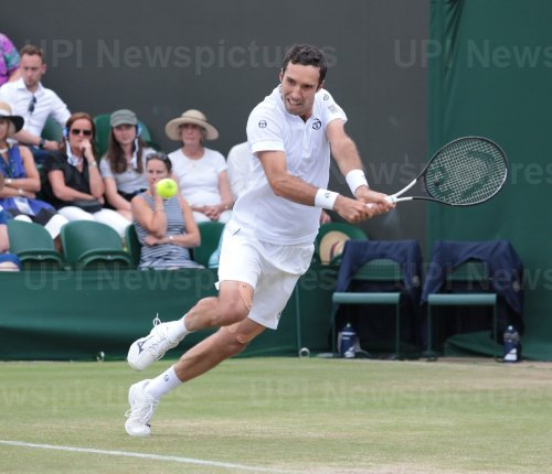 Mikhail Kukuskin returns in his fourth round match against Kei Nishikori at Wimbledon