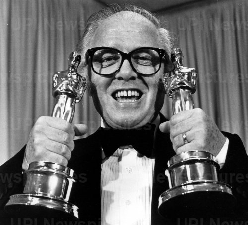 """Richard Attenborough holds up two Oscars for the movie, """"Gandhi."""""""
